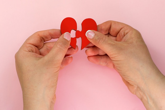 Dos manos sosteniendo la conexión de dos piezas rompecabezas amor corazón rompecabezas, concepto de amor