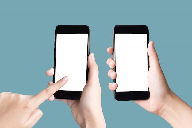 Dos manos sosteniendo y jugando smartphone con pantalla en blanco
