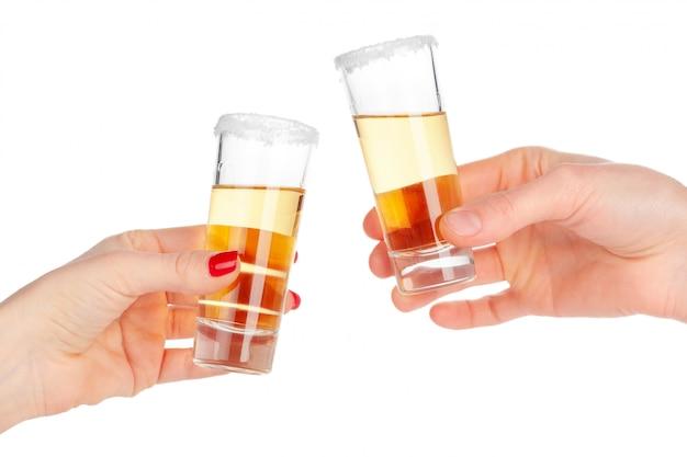 Dos manos tintinean vasos con cóctel de tiro sobre fondo blanco.