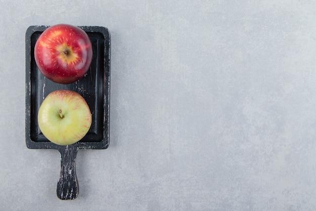Dos manzanas frescas en la tabla de cortar negra