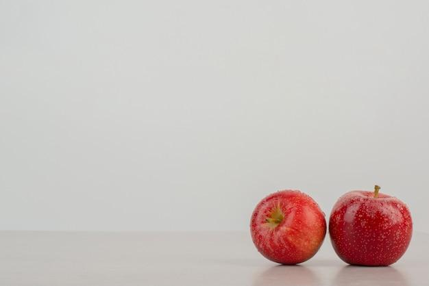 Dos manzanas rojas sobre la mesa de mármol.