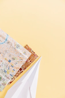 Dos mapas de la ciudad con avión de papel hecho a mano en la esquina del fondo.