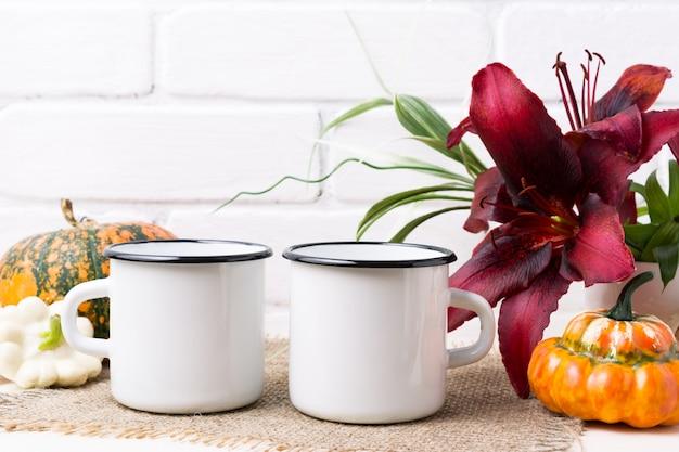 Dos maquetas de taza de esmalte de fogata blanca con calabaza y lirio