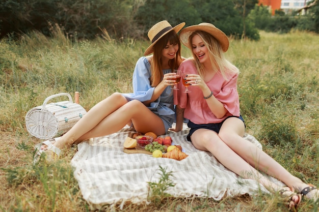 Dos maravillosas chicas con sombrero de paja pasando las vacaciones en el campo, bebiendo vino espumoso.