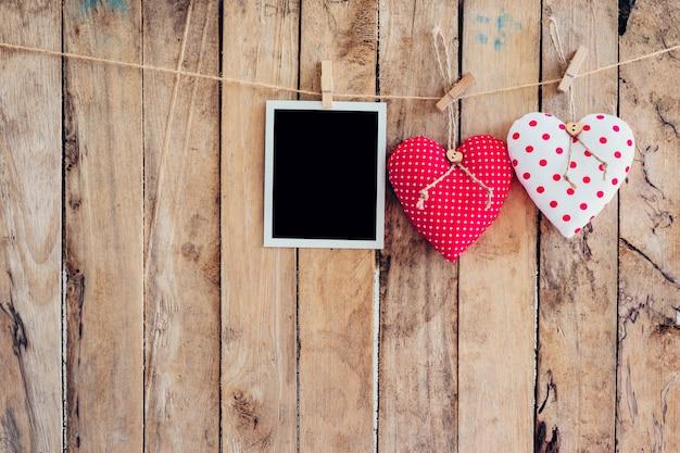 Dos marco del corazón y de la foto que cuelgan en cuerda de la cuerda para tender la ropa con el fondo de madera.