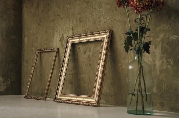 Dos marcos dorados en el suelo y florero.