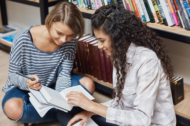 Dos más exitosas estudiantes multiétnicas en ropa casual sentados en el piso de la biblioteca de la universidad