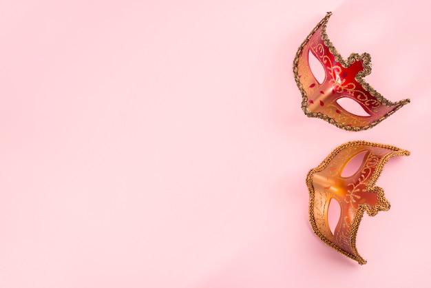 Dos máscaras de carnaval en mesa rosa
