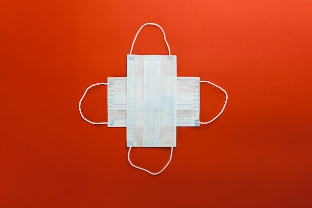 Dos máscaras de protección médica respiratoria se encuentran en forma de cruz sobre un fondo rojo.