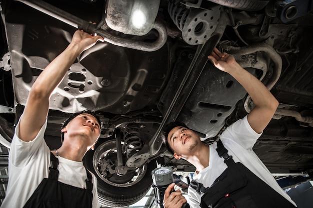Dos mecánicos estaban revisando la suspensión del auto.