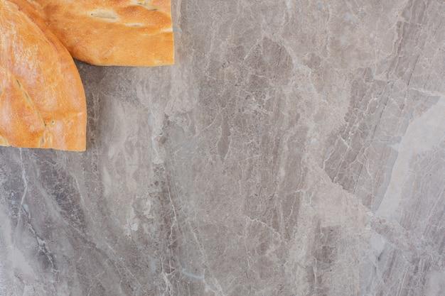 Dos medias hogazas de pan tandoori sobre mármol.