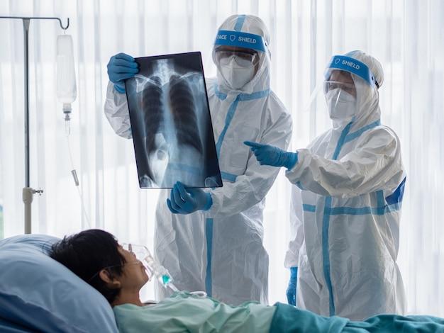 Dos médicos asiáticos usan traje de ppe con máscara n95 y protector facial, examinan una película de rayos x de tórax pulmonar de un paciente infectado con coronavirus en una sala de presión negativa.
