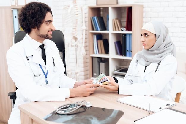 Dos médicos comparten dinero entre ellos en la clínica.