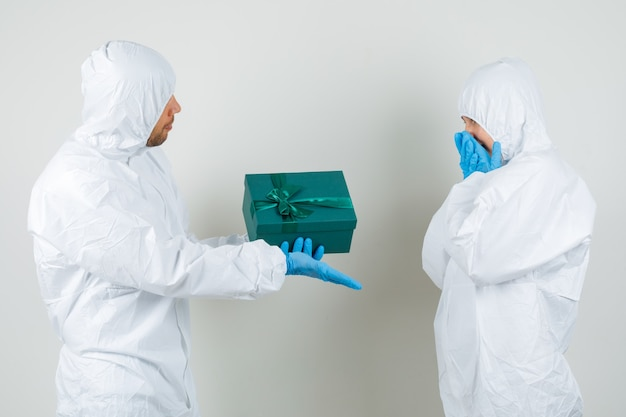 Dos médicos dando caja presente entre sí en traje protector