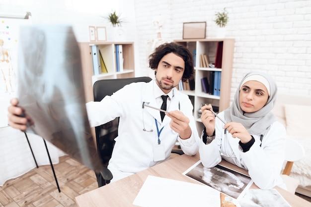 Dos médicos están examinando una radiografía de un paciente enfermo.