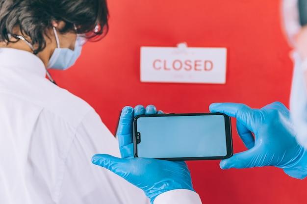 Dos médicos con guantes azules, mascarillas y batas blancas controlan un análisis de sangre con un teléfono inteligente en la mano.