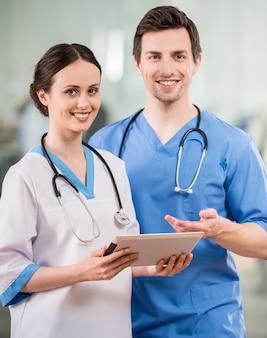 Dos médicos jóvenes con tableta digital en el consultorio del médico.