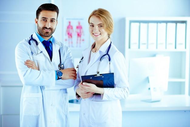 Dos médicos de razas mixtas, todos parados juntos en una sala de consulta y sosteniendo notas de pacientes
