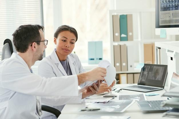 Dos médicos sentados a la mesa y examinar la tarjeta médica del paciente juntos y discutirlo