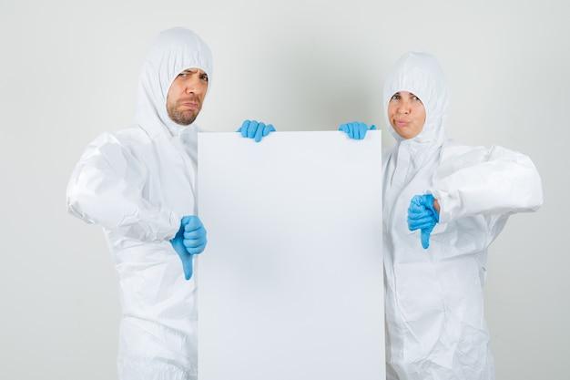 Dos médicos sosteniendo un lienzo en blanco y mostrando los pulgares hacia abajo en trajes protectores