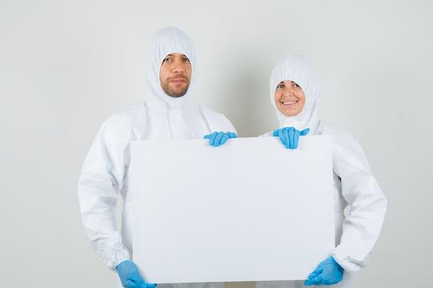 Dos médicos sosteniendo un lienzo en blanco en trajes de protección, guantes y mirando feliz