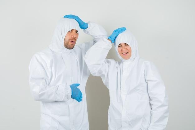 Dos médicos tomados de la mano en la cabeza con trajes protectores