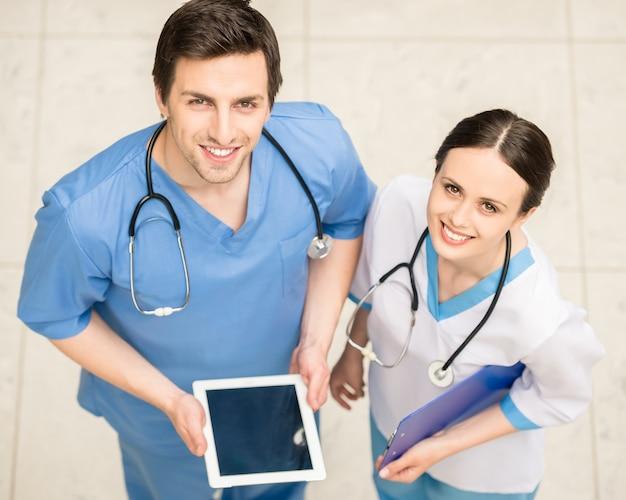 Dos médicos trabajando junto con tableta digital.