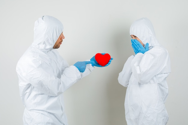 Dos médicos en traje de protección, guantes dando corazón rojo el uno al otro