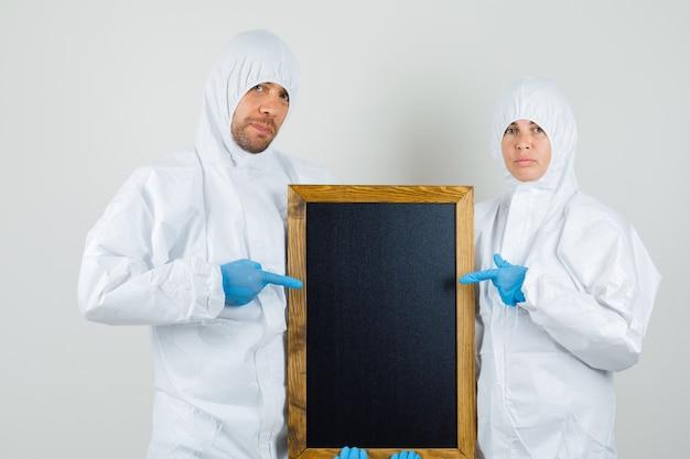Dos médicos en trajes de protección, guantes apuntando a la pizarra y mirando confiados