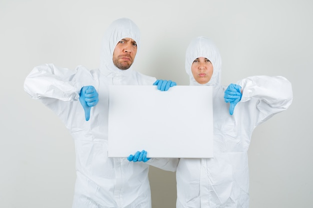 Dos médicos en trajes de protección, guantes con lienzo en blanco
