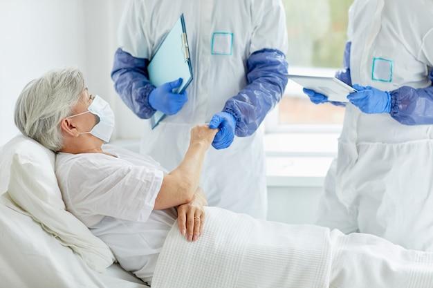 Dos médicos con trajes de protección con guantes que examinan la salud del paciente mayor en la sala de enfermedades infecciosas