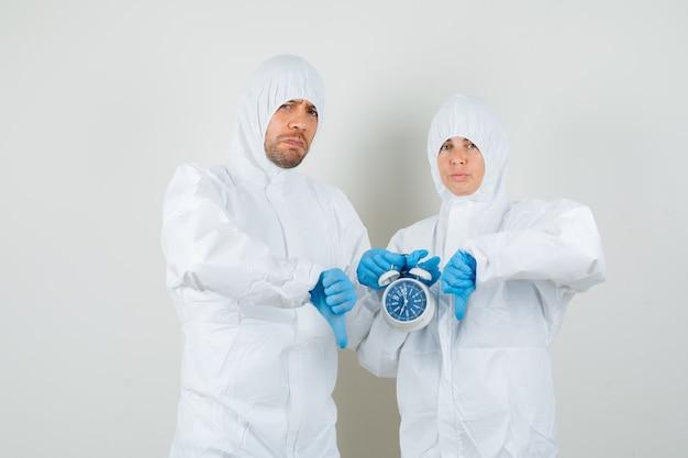 Dos médicos en trajes de protección, guantes con reloj despertador