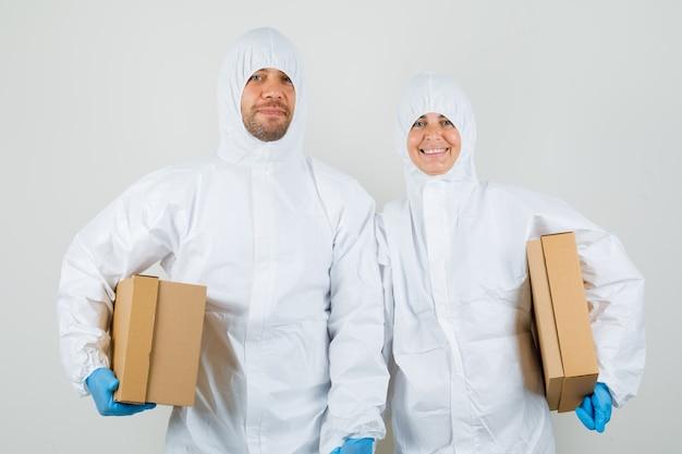 Dos médicos en trajes de protección, guantes sosteniendo cajas de cartón y mirando alegres