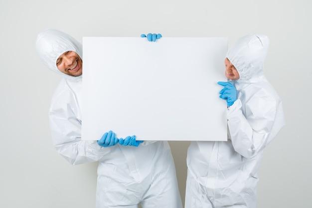 Dos médicos en trajes de protección, guantes sosteniendo un lienzo vacío y mirando feliz