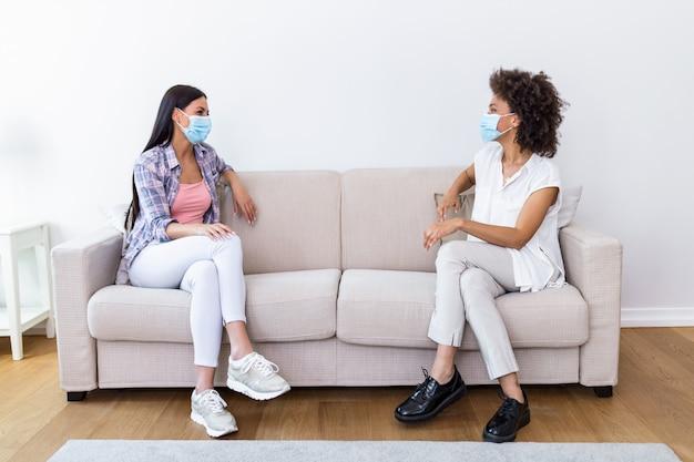 Dos mejores amigas sentadas en la distancia social usando una máscara facial y hablando en el sofá, evitando la propagación de la infección por el covid 19 coronavirus.