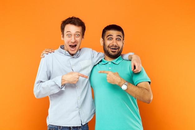 Dos mejores amigos abrazándose señalando con el dedo y mirando a la cámara con cara de sorpresa