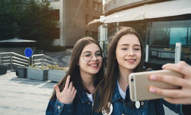 Dos mejores amigos felices que transmiten videos en vivo en la calle de la ciudad
