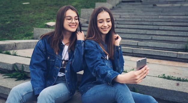 Dos mejores amigos felices que usan las redes sociales en sus teléfonos inteligentes