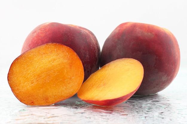 Dos melocotones maduros sobre un fondo blanco. alimento vitamínico útil de fruta.