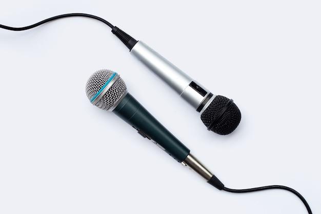 Dos micrófonos sobre fondo blanco.