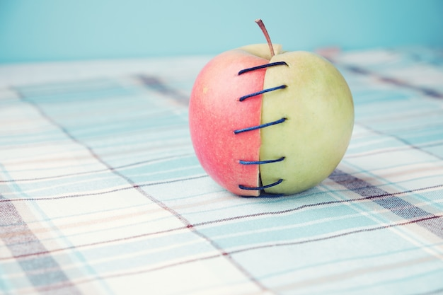 Dos mitades diferentes de manzana conectadas por hilo