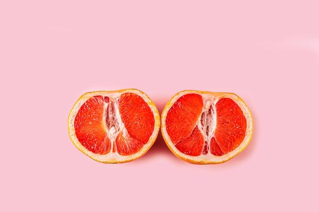 Dos mitades de pomelo rojo fresco cortado en superficie rosa. concepto de salud femenina. fruta como símbolo de la vagina. de cerca.