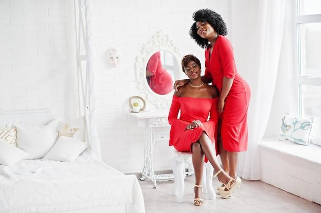 Dos modelos afroamericanos de moda en vestido de belleza rojo, mujer sexy posando vestido de noche en la sala blanca vintage.
