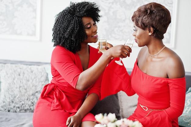 Dos modelos afroamericanos de moda en vestido de belleza rojo, mujer sexy posando vestido de noche sentado en el sofá y bebiendo champán de copas.