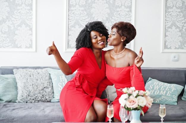 Dos modelos afroamericanos de moda en vestido de belleza rojo, mujer sexy posando vestido de noche sentado en el sofá y divertirse juntos.