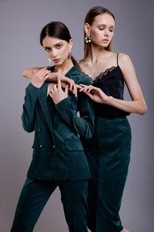 Dos modelos de moda en traje verde y falda superior negra hermosas mujeres jóvenes fondo gris