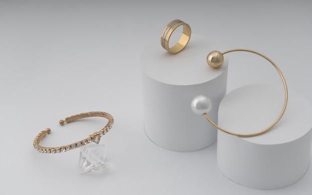 Dos modernas pulseras doradas y un anillo dorado en una configuración de papel blanco