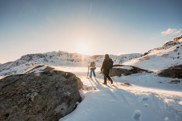 Dos montañeros senderismo a pico de montaña en campo de nieve al atardecer