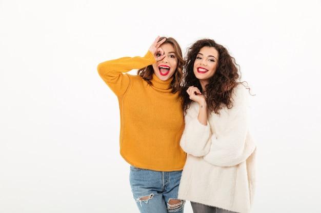 Dos muchachas alegres en suéteres divirtiéndose juntos sobre la pared blanca