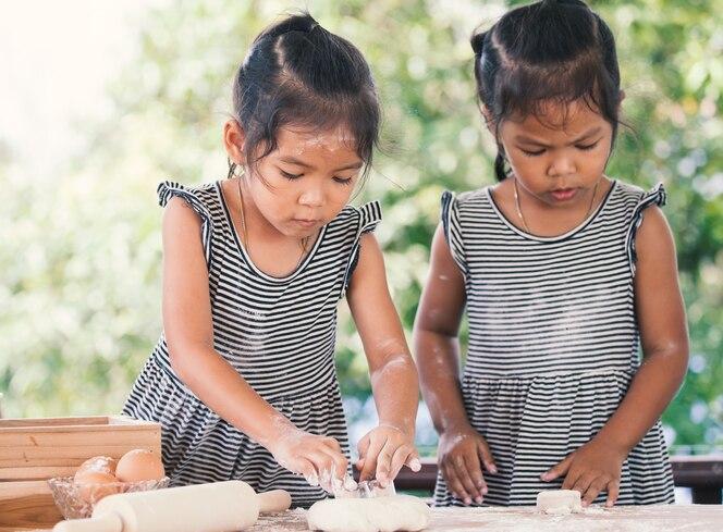 Dos muchachas asiáticas lindas del niño preparan una pasta para cocer las galletas en la cocina